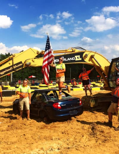 Group stand over a car with excavator in background on July 4