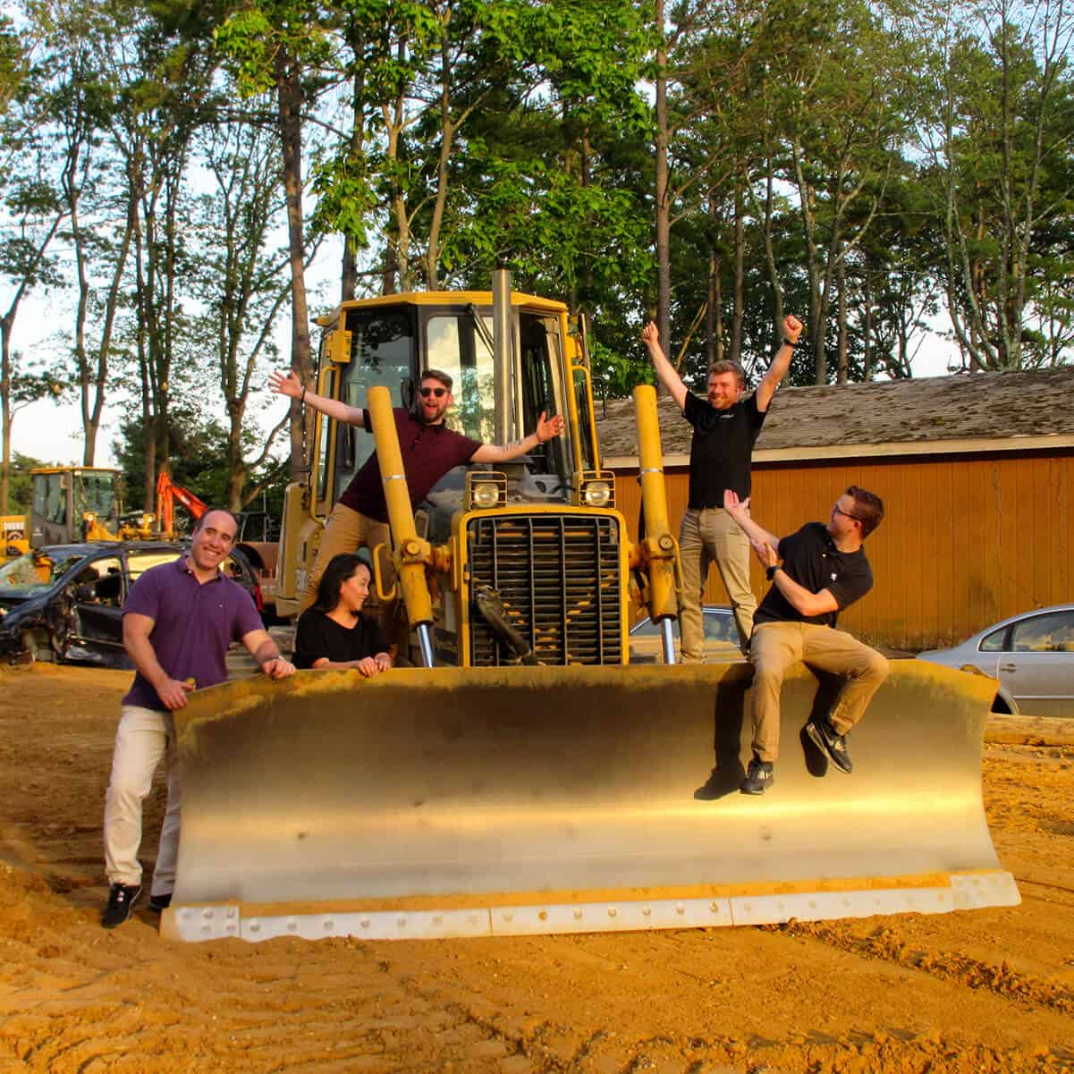 Corporate group sits on top of a bulldozer posing for the camera