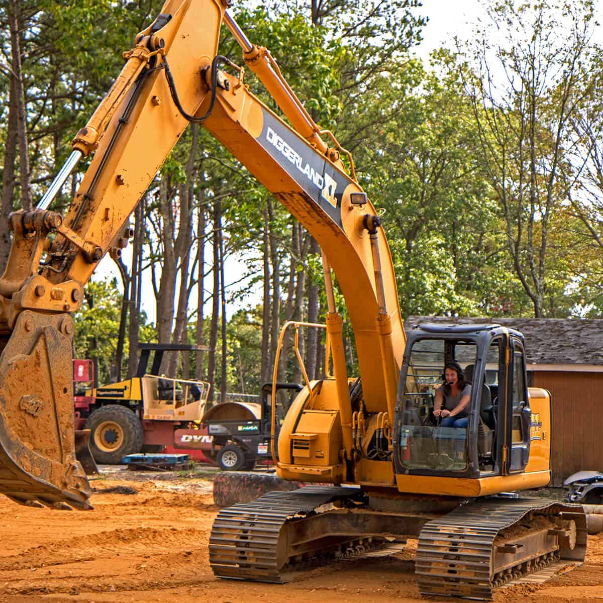 Woman operating an excavator during a team building event