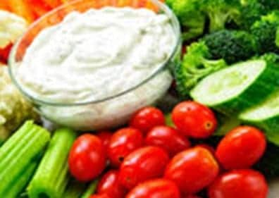 Tomatoes, celery, broccoli and cucumbers surrounding ranch dressing