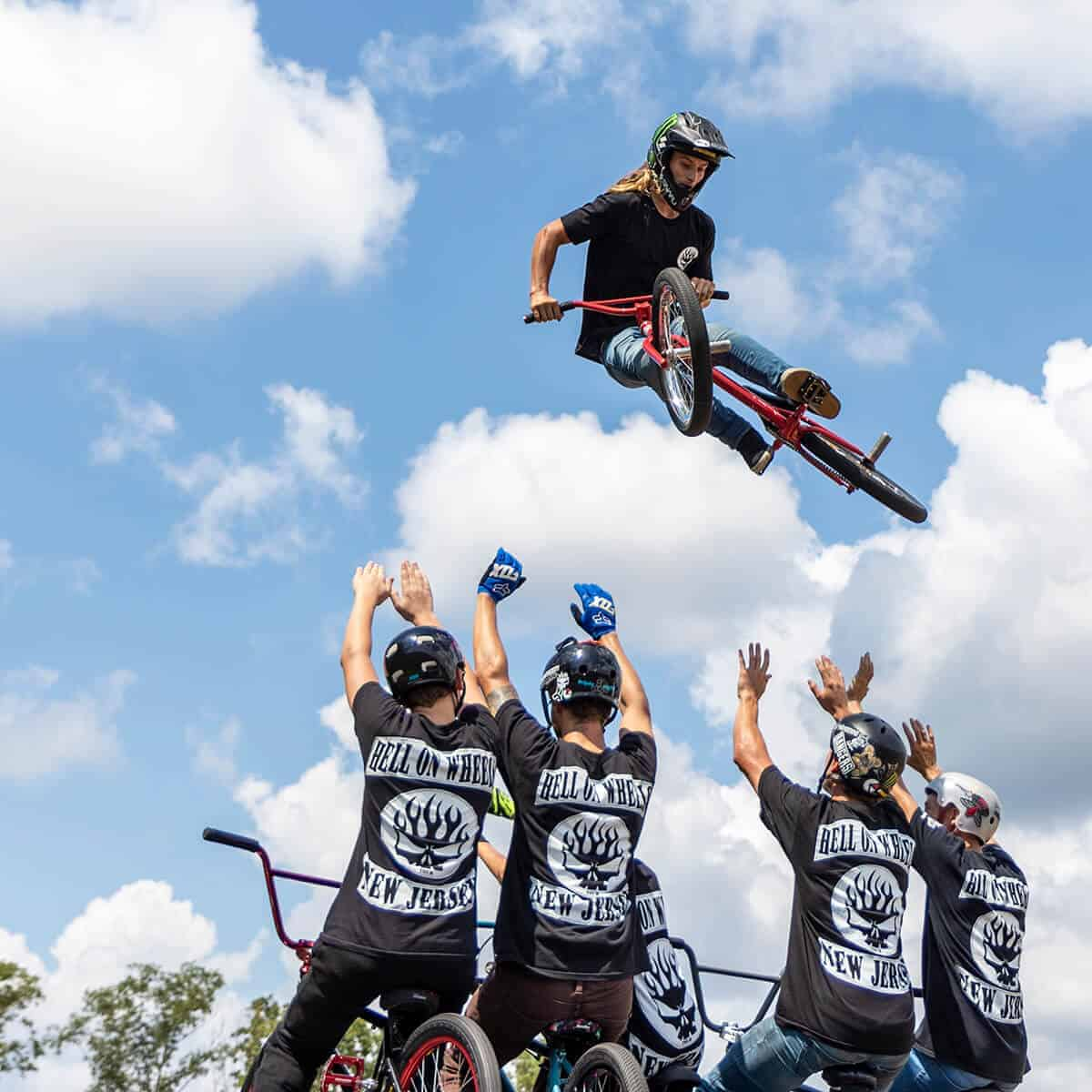 BMX rider leaping over other BMX riders at special event