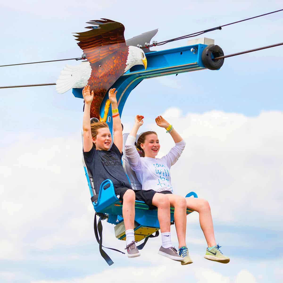 Boy and girl with arms up on Soaring Eagle zip line