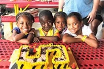 Boys and girls seated in front of a construction-themed birthday cake