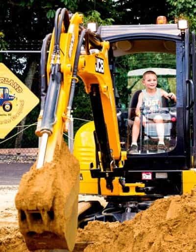 Child smiles while digging dirt in the Big Digger