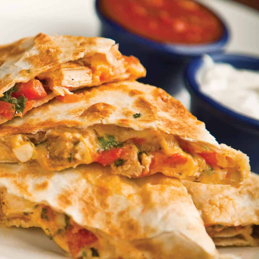 Cheesy chicken quesadillas with salsa and sour cream