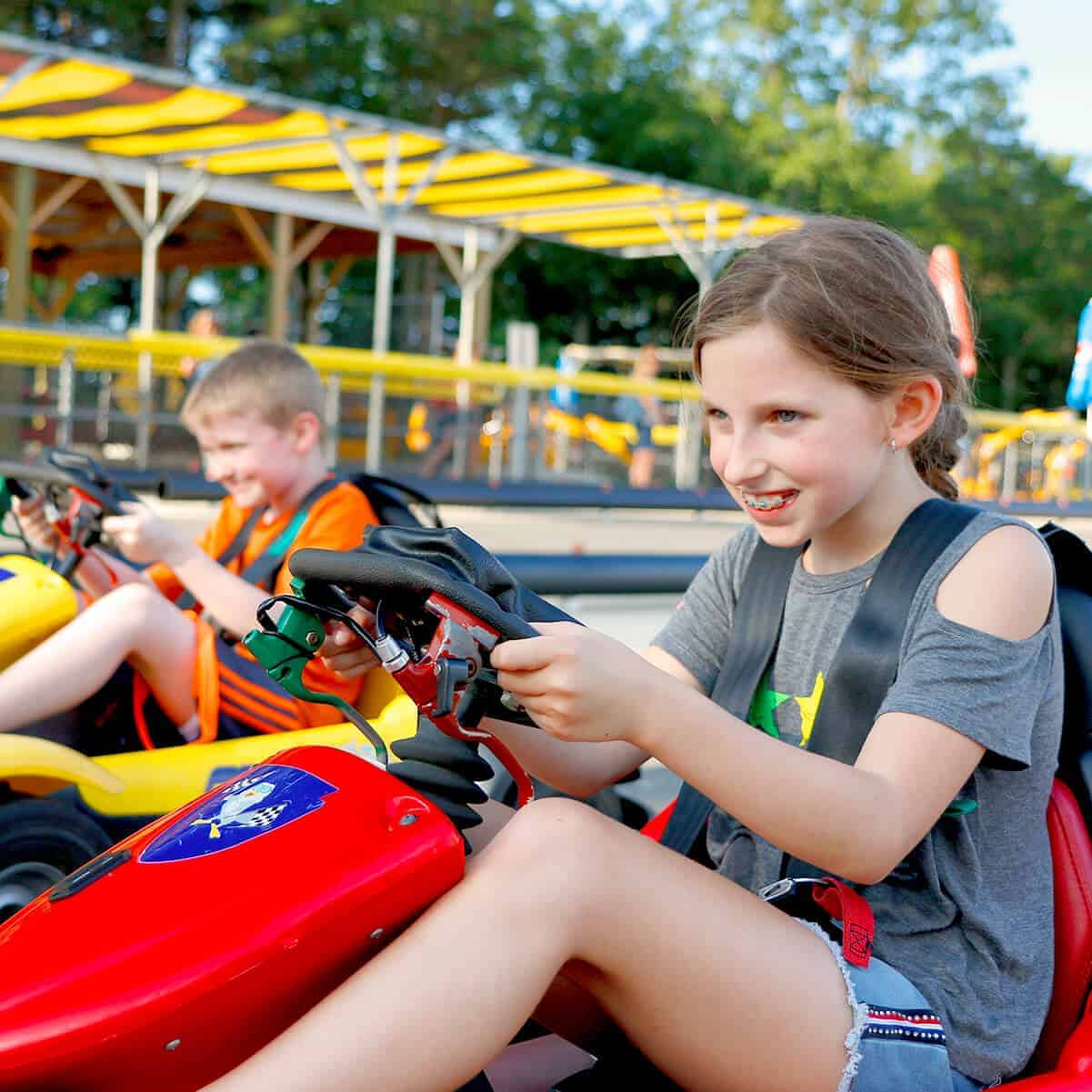 Boy and girl race on Digger Derby go carts on special course at Diggerland USA