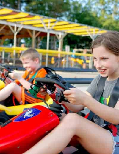 Girl races boy on Digger Derby go-carts.