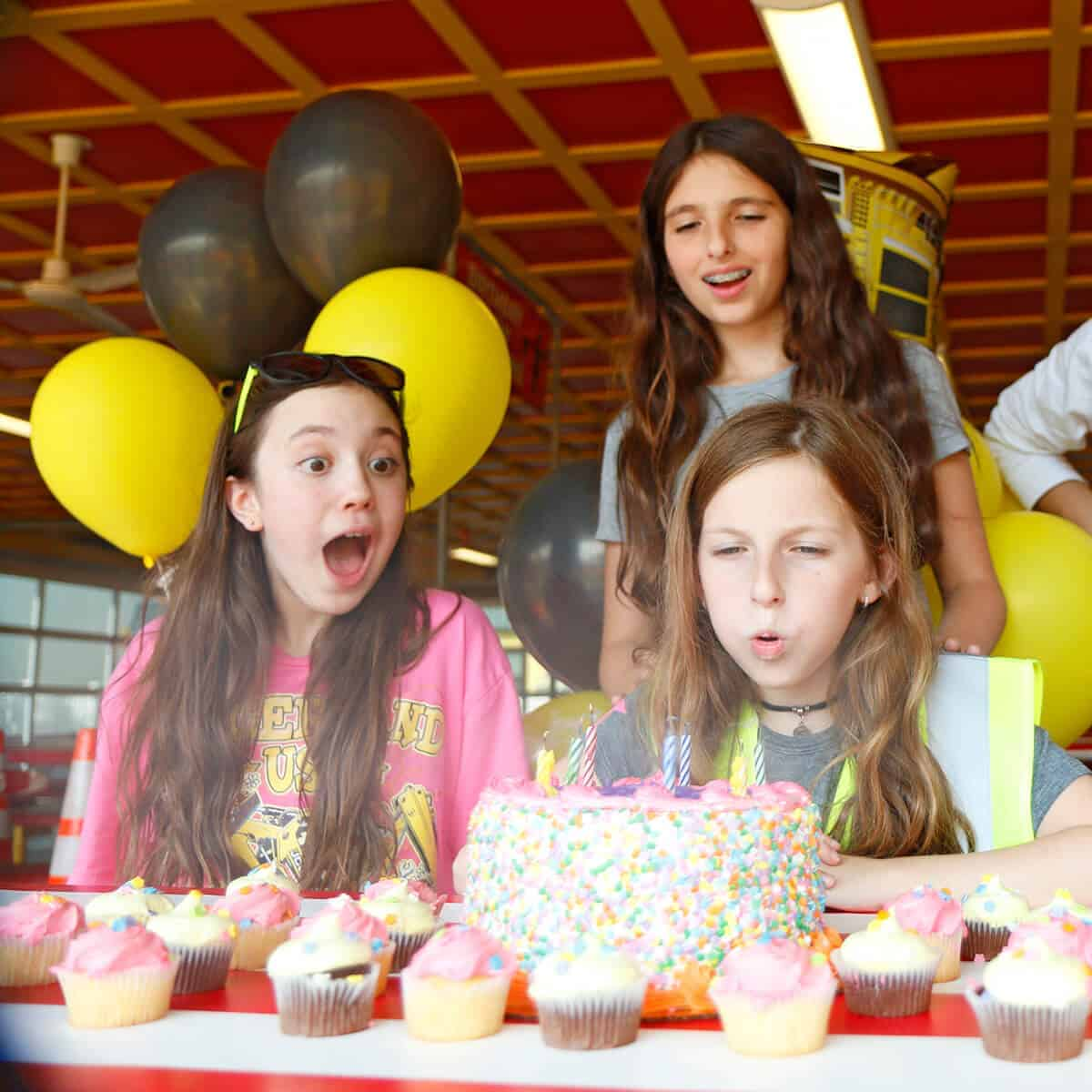 Girl blowing out candles at a custom birthday party at Diggerland