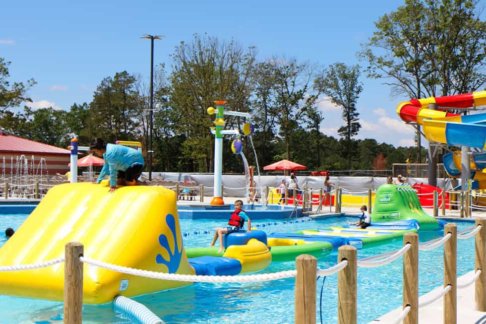 Boy and girl climb on water obstacle course laughing and splashing