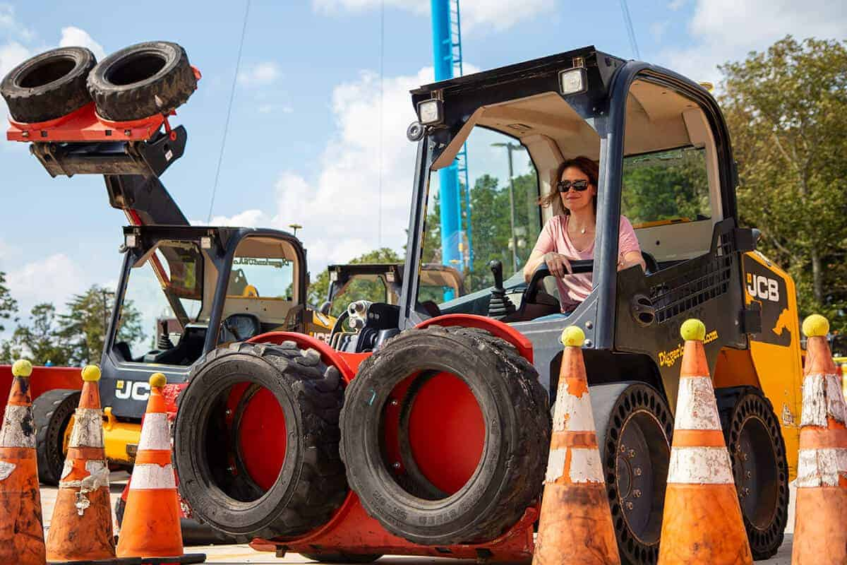 Woman avoiding cones on skid-steer during team building exercise