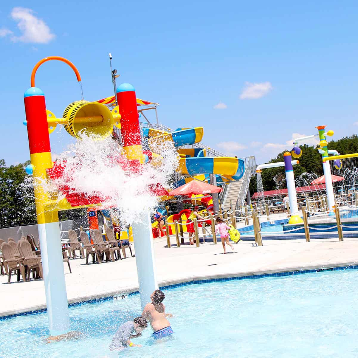 Kids enjoying our all new water park splash pads with construction-themed water bucket
