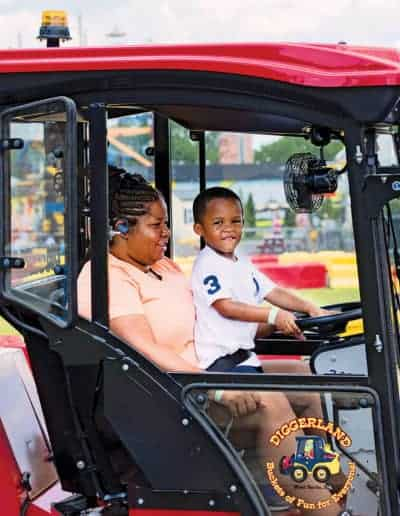 Child steers the Ventrac on Mother's lap