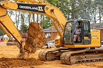 Older man driving an excavator for fun and digging up dirt